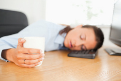 A sleeping businesswoman is holding a cup of coffee in an office